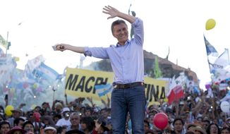 In this Thursday, Nov. 19, 2015 photo, opposition presidential candidate Mauricio Macri waves to supporters during the closing campaign rally in Humahuaca, Jujuy, Argentina. Macri will face the ruling party candidate Daniel Scioli in a Nov. 22 runoff. (AP Photo/Natacha Pisarenko)