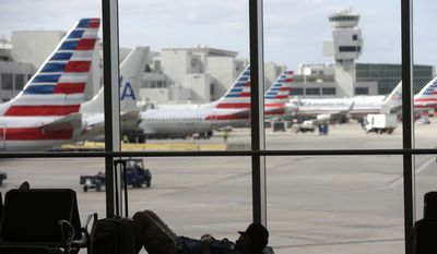 A traveler rests on the floor as American Airlines aircraft are lined up the the gates at Miami International Airport, Tuesday, Nov. 24, 2015, in Miami. Thanksgiving is one of the busiest travel holidays of the year, both in the air and on the roads. (AP Photo/Lynne Sladky) ** FILE **