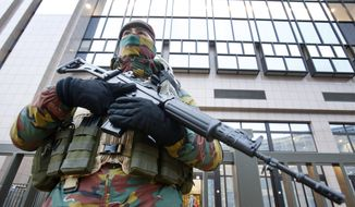 A Belgian police officer guards the building of the European Commission in Brussels, Belgium, Tuesday, Nov. 24, 2015. Brussels is keeping its terror alert at the highest level. (AP Photo/Michael Probst)