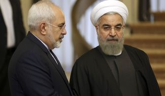 Iranian President Hassan Rouhani, right, listens to his Foreign Minister Mohammad Javad Zarif prior to their meeting with Nigerian President Muhammadu Buhari in Tehran, Iran, Tuesday, Nov. 24, 2015. (AP Photo/Vahid Salemi)