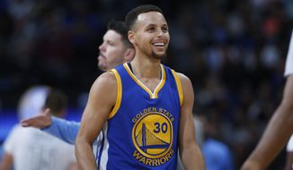 Golden State Warriors guard Stephen Curry jokes with teammates after hitting a 3-point shot against the Denver Nuggets during the first half of an NBA basketball game Sunday, Nov. 22, 2015, in Denver. (AP Photo/David Zalubowski)