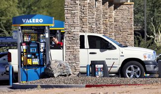 A motorist fuels his vehicle Tuesday, Nov. 24, 2015, in Gilbert, Ariz. With Thanksgiving gas prices at its cheapest since 2008, the number of travelers is expected to rise. (AP Photo/Matt York)