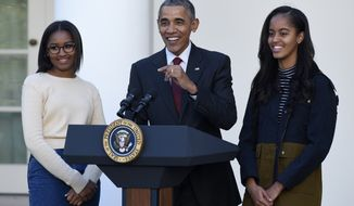 President Barack Obama, with his daughters, Sasha, left, and Malia, speaks before he pardoned the National Thanksgiving Turkey Abe, Wednesday, Nov. 25, 2015, during a ceremony in the Rose Garden of the White House in Washington. This is the 68th anniversary of the National Thanksgiving Turkey presentation (AP Photo/Susan Walsh)