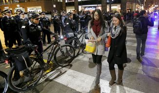 Pedestrians walk past a phalanx of Chicago police officers keeping protesters off Wacker Drive, Wednesday, Nov. 25, 2015, in Chicago, the day after murder charges were brought against police officer Jason Van Dyke in the killing of 17-year-old Laquan McDonald. (AP Photo/Charles Rex Arbogast)