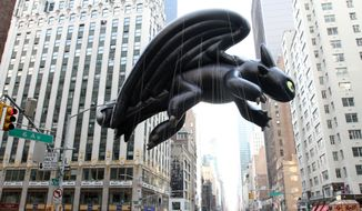"""The Toothless balloon, from """"How To Train Your Dragon"""" makes its way down New York's Sixth Avenue during the Macy's Thanksgiving Day Parade Thursday, Nov. 26, 2015. (AP Photo/Tina Fineberg)"""