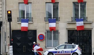 People drapped in the national flag walk past a building decorated with French flags in Paris, Friday, Nov. 27, 2015. French President Francois Hollande called on his compatriots to hang French tricolor flags on Friday to pay homage to the 130 victims of the Nov. 13 attacks, an unusual appeal by a Socialist leader in a country where flag-waving is often associated with nationalists and the far right. (AP Photo/Francois Mori)