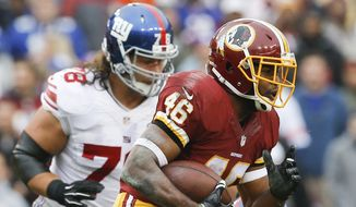 Washington Redskins running back Alfred Morris (46) carries the ball past New York Giants defensive tackle Markus Kuhn (78) during the first half of an NFL football game in Landover, Md., Sunday, Nov. 29, 2015. (AP Photo/Patrick Semansky)