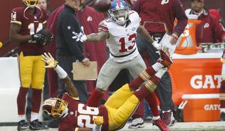 New York Giants wide receiver Odell Beckham (13) and Washington Redskins cornerback Bashaud Breeland (26) both reach for an overthrown Eli Manning pass during the first half of an NFL football game in Landover, Md., Sunday, Nov. 29, 2015. (AP Photo/Alex Brandon)