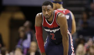 Washington Wizards' John Wall (2) watches a free throw in the second half of an NBA basketball game against the Charlotte Hornets in Charlotte, N.C., Wednesday, Nov. 25, 2015. The Hornets won 101-87. (AP Photo/Chuck Burton)