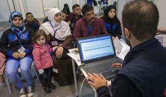 A family of Syrian refugees are interviewed by authorities in hope of being approved for passage to Canada at a refugee processing center in Amman, Jordan, Sunday, Nov. 29, 2015. A trickle of Syrian refugees seeking to leave Jordan flowed into Canada's processing centre in Amman on Sunday, the first day of operations at what will eventually become the hub of much of the Syrian refugee resettlement program, according to The Canadian Press. (Paul Chiasson/The Canadian Press via AP) MANDATORY CREDIT
