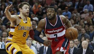 Washington Wizards' John Wall (2) drives past Cleveland Cavaliers' Matthew Dellavedova (8), from Australia, in the first half of an NBA basketball game Tuesday, Dec. 1, 2015, in Cleveland. (AP Photo/Tony Dejak)