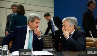 U.S. Secretary of State John Kerry, left, speaks with Belgian Foreign Minister Didier Reynders, before a session on Ukraine at the NATO ministerial meetings at NATO Headquarters in Brussels, Wednesday Dec. 2, 2015. (Jonathan Ernst/ Pool via AP)