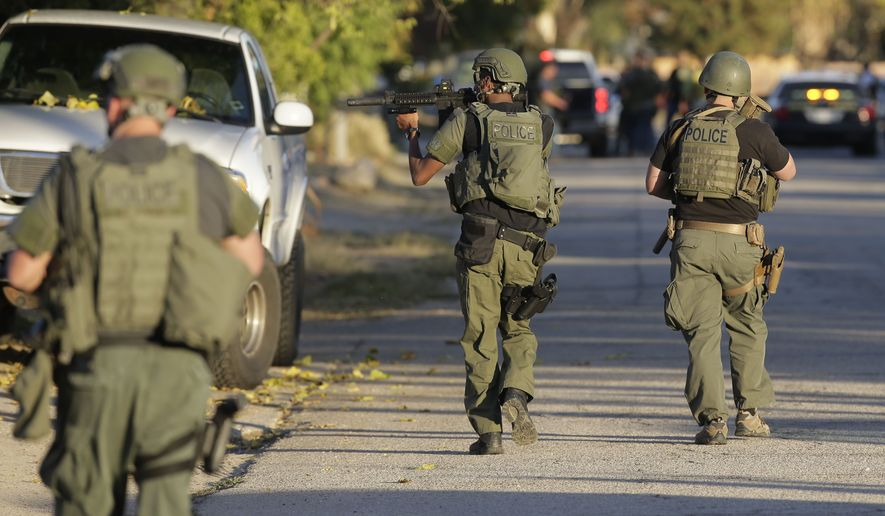 Law enforcement searches for a suspect in a mass shooting at a social services center Wednesday in San Bernardino, Calif. (Associated Press)
