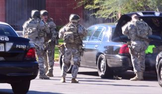 A SWAT team arrives at the scene of a shooting in San Bernardino, Calif., on Dec. 2, 2015.  Police responded to reports of an active shooter at a social services facility. (Doug Saunders/Los Angeles News Group via AP)