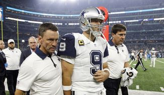 Team staff escort Dallas Cowboys quarterback Tony Romo (9) off the field after Romo suffered an unknown injury after being sacked by Carolina Panthers outside linebacker Thomas Davis in the second half of an NFL football game, Thursday, Nov. 26, 2015, in Arlington, Texas. (AP Photo/Brandon Wade)