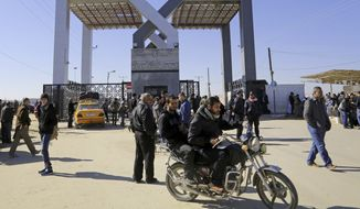 Palestinians wait to cross the border to the Egyptian side at the Rafah crossing, in the southern Gaza Strip, int his Tuesday, Jan. 20, 2015, file photo. (AP Photo/Adel Hana, File)