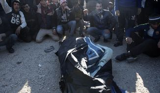 Stranded migrants shouts slogans next a covered body of a man believed to be from Morocco, at the Greek-Macedonian border, near the northern Greek village of Idomeni, Thursday, Dec. 3, 2015. The man was electrocuted after touching high-power overhead railway cables when he climbed on top of a train carriage. (AP Photo/Giannis Papanikos)