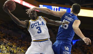 UCLA guard Aaron Holiday, left, attempts a shot as Kentucky forward Isaac Humphries defends during the first half of an NCAA college basketball game in Los Angeles, Thursday, Dec. 3, 2015. (AP Photo/Kelvin Kuo)