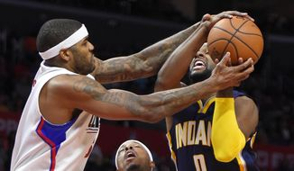 Los Angeles Clippers center Josh Smith, left, ties up Indiana Pacers forward C.J. Miles, right, as Clippers' forward Paul Pierce stands between during the first half of an NBA basketball game, Wednesday, Dec. 2, 2015, in Los Angeles. (AP Photo/Mark J. Terrill)