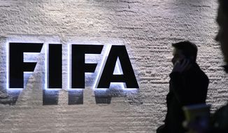 "A man stands in front of the logo at the FIFA headquarters ""Home of FIFA"" in Zurich, Switzerland, in this Dec. 2, 2015, file photo. (Walter Bieri/Keystone via AP)"