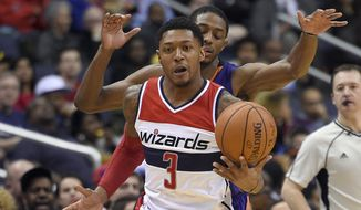 Washington Wizards guard Bradley Beal (3) head downcourt with the ball in front of Phoenix Suns guard Brandon Knight, back, during the second half of an NBA basketball game, Friday, Dec. 4, 2015, in Washington. (AP Photo/Nick Wass)