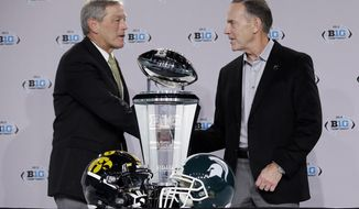 Iowa head coach Kirk Ferentz, left, and Michigan State head coach Mark Dantonio shake hands during a news conference for the Big Ten Conference championship NCAA college football game Friday, Dec. 4, 2015, in Indianapolis. Iowa will play Michigan State Saturday for the championship. (AP Photo/Darron Cummings)
