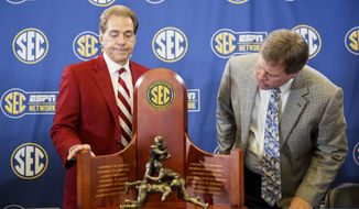Alabama head coach Nick Saban, left, and Florida head coach Jim McElwain look down at the trophy during a press conference held ahead of Saturday's Southeastern Conference championship NCAA college football game, Friday, Dec. 4, 2015, in Atlanta. (AP Photo/David Goldman)