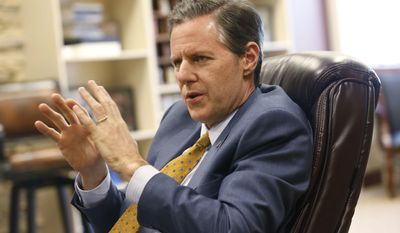 In this April 21, 2015, file photo, Liberty University president, Jerry Falwell Jr., gestures during an interview at the school in Lynchburg, Va. Virginia's governor is criticizing Falwell for urging his Christian college community to arm itself against a possible attack by a would-be mass killer. Falwell made the suggestion at a gathering of 10,000 on the Lynchburg campus on Friday, Dec. 4. (AP Photo/Steve Helber, File)