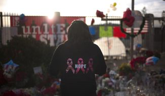 Jennifer Wheeler pays respects at a makeshift memorial honoring the victims of Wednesday's shooting rampage that killed multiple people, Sunday, Dec. 6, 2015, in San Bernardino, Calif. (AP Photo/Jae C. Hong)