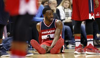 Washington Wizards guard John Wall (2) holds his leg as he sits on the court in the second half of an NBA basketball game against the Dallas Mavericks, Sunday, Dec. 6, 2015, in Washington. The Mavericks won 116-104. (AP Photo/Alex Brandon)