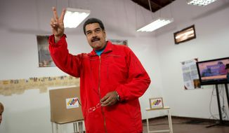 Venezuela's President Nicolas Maduro flashes a victory sign before voting during congressional elections in Caracas, Venezuela, Sunday, Dec. 6, 2015. (AP Photo/Ariana Cubillos)
