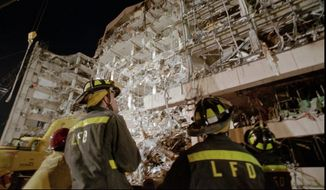 Fire personnel gather at the base of the Alfred P. Murrah Federal Building in downtown Oklahoma City on April 20, 1995, the day after the bombing. (Associated Press)