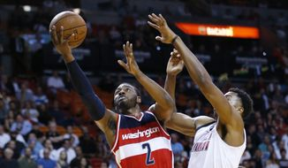 Washington Wizards guard John Wall (2) goes up for a shot against Miami Heat center Hassan Whiteside (21) during the first half of an NBA basketball game, Monday, Dec. 7, 2015, in Miami. (AP Photo/Wilfredo Lee)