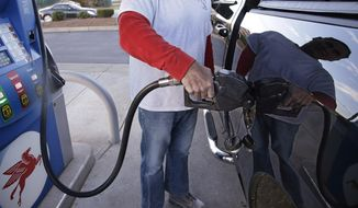A customers prepares to pump gas on Monday, Dec. 7, 2015, at a gas station in Pembroke, Mass. The price of a barrel of oil fell Monday to a nearly seven-year low. With OPEC's decision to keep pumping at current levels, analysts expect oil to remain relatively cheap well into 2016 and maybe longer. (AP Photo/Stephan Savoia)