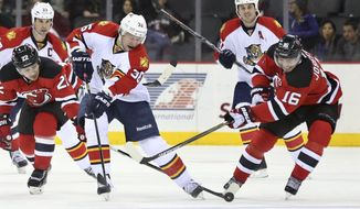 Florida Panthers left wing Jussi Jokinen, of Finland, (36) and New Jersey Devils center Jacob Josefson, of Sweden,(16) skate for the puck during the first period of an NHL hockey game Sunday, Dec. 6, 2015, in Newark, N.J. (AP Photo/Mel Evans)