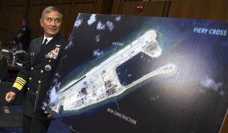 Adm. Harry B. Harris Jr., commander of U.S. Pacific Command, shows a photograph of an island that China is building on the Fiery Cross Reef in the South China Sea. (Associated Press/File)