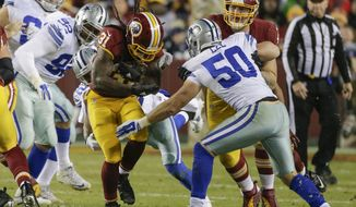 Washington Redskins running back Matt Jones (31) carries the ball past Dallas Cowboys outside linebacker Sean Lee (50) during the first half of an NFL football game in Landover, Md., Monday, Dec. 7, 2015. (AP Photo/Mark Tenally)