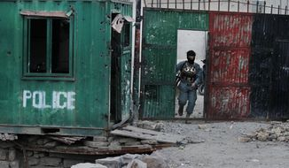 An Afghan security man inspects damages after clashes between the Afghan police and Taliban militants at a police station in the city of Kandahar, south of Kabul, Afghanistan, Tuesday, Dec. 8, 2015. (AP Photo/Allauddin Khan)