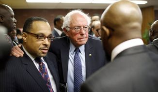 Democratic presidential candidate, Sen. Bernie Sanders, I-Vt., center, puts his arm around Rev. Todd Yeary of Baltimore, as he speaks with African-American civic and religious leaders at the Freddie Gray Empowerment Center in Baltimore, Tuesday, Dec. 8, 2015, after taking a walking tour of Gray's neighborhood and participating in a roundtable discussion on issues affecting the African-American community. (AP Photo/Patrick Semansky)
