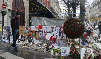 A member of the band Eagles of Death Metal, Jesse Hughes, pays his respects to 89 victims who died in a Nov. 13 attack, at the Bataclan concert hall in Paris, France, Tuesday, Dec. 8, 2015. Members of the California rock band Eagles of Death Metal are back at the ravaged Paris theater where they survived a massacre by Islamic extremist suicide bombers. (AP Photo/Jacques Brinon)