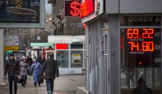 People walk past an exchange office sign showing the currency exchange rates of Russian ruble, U.S. dollar, and euro in Moscow, Russia, Tuesday, Dec. 8, 2015. The ruble continued to decline on Tuesday as oil prices are reaching a seven-year low.  (AP Photo/Alexander Zemlianichenko)