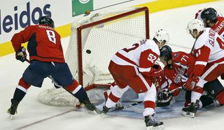 Washington Capitals left wing Alex Ovechkin (8) scores the tying goal past Detroit Red Wings goalie Jimmy Howard (35) with Red Wings defenseman Jonathan Ericsson (52) nearby in the third period of an NHL hockey game, Tuesday, Dec. 8, 2015, in Washington. The Capitals won 3-2 in a shootout. (AP Photo/Alex Brandon)