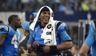 A smiling Carolina Panthers quarterback Cam Newton walks near the team bench late in the second half of the Panthers' NFL football game against the Dallas Cowboys, Thursday, Nov. 26, 2015, in Arlington, Texas. The Panthers won 33-14. (AP Photo/Michael Ainsworth)