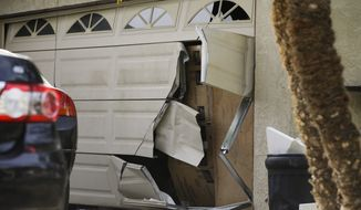 A garage door of Enrique Marquez's home is seen broken in a recent FBI raid, Wednesday, Dec. 9, 2015, in Riverside, Calif. Authorities have said Enrique Marquez, an old friend of San Bernardino attacker Syed Farook, purchased two assault rifles used in last week's fatal shooting that killed 14 people. (AP Photo/Jae C. Hong)