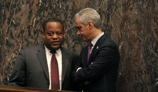 "Chicago Alderman Roderick Sawyer left, talks with Chicago Mayor Rahm Emanuel right, before Emanuel spoke during a special City Council meeting that he called to discuss a police abuse scandal Wednesday, Dec. 9, 2015, in Chicago. Emanuel apologized for the 2014 shooting of a black teenager Wednesday during the special City Council meeting and promised ""complete and total"" reform to restore trust in the police.  (AP Photo/Paul Beaty)"