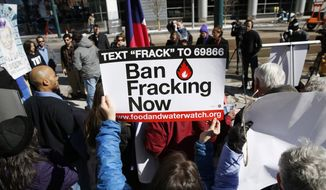 In this file photograph taken on Feb. 24, 2015, an activist waves a placard calling for the ban of fracking during a news conference outside the Colorado Convention Center in Denver as the Oil and Gas Task Force meets inside the facility to put the final touches on recommendations for Colorado Gov. John Hickenlooper to consider in the settlement of disputes over oil and gas well development. The Colorado Supreme Court will hear arguments Wednesday, Dec. 9, 2015, in a high-stakes battle over whether local governments can impose tougher rules on oil and gas producers than the state. (AP Photo/David Zalubowski, File)