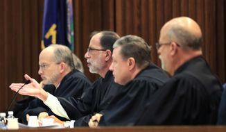 Kansas Court of Appeals Judge G. Gordon Atcheson, second from left, asks questions of appellant counsel during oral arguments in Topeka, Kan., Wednesday, Dec. 9, 2015.  The lawsuit against a Kansas ban on a common second-trimester procedure has forced the state Court of Appeals to consider how much the state constitution protects abortion rights. (AP Photo/Orlin Wagner)