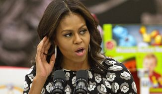 First lady Michelle Obama listens for a shout out from members of the military as she speaks before sorting toys as part of the Marine Corps Toys for Tots program, Wednesday, Dec. 9, 2015, at Bolling Air Force Base in Washington. (AP Photo/Jacquelyn Martin)