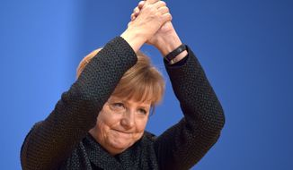 FILE - In this Tuesday, Dec. 9, 2014, file photo, German Chancellor and chairwoman of the  Christian Democrats, CDU, Angela Merkel, thanks delegates for their standing ovations after her speech at the party convention in Cologne, Germany. Merkel has been named as Time's Person of the Year, the publication announced Wednesday, Dec. 9, 2015, praised by the magazine for her leadership on everything from Syrian refugees to the Greek debt crisis. (AP Photo/Martin Meissner, File)