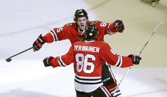Chicago Blackhawks center Andrew Shaw (65) celebrates his goal with Teuvo Teravainen during the second period of an NHL hockey game against the Nashville Predators, Tuesday, Dec. 8, 2015, in Chicago. (AP Photo/Charles Rex Arbogast)